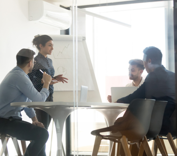 A female discussing with her male colleagues in the office