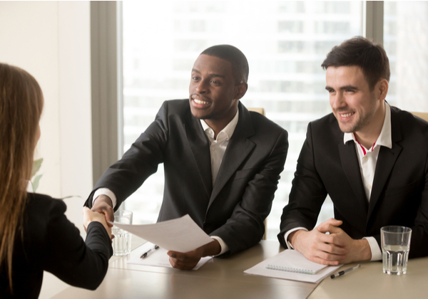Two men cheerfully interviewing an applicant