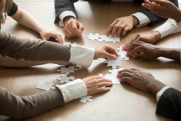 Business people assembling the puzzle together